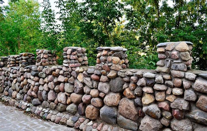 Забор из камня (58 фото): каменная ограда в сетке, варианты из декоративного камня и бута